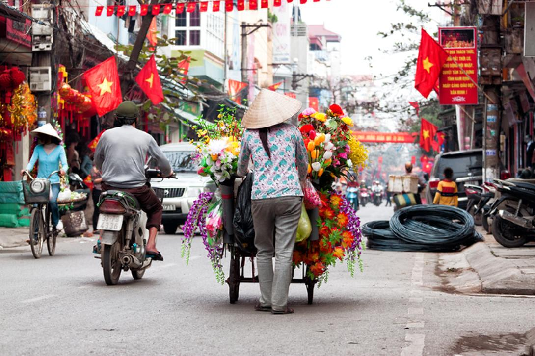 A busy street in Vietnam with merchants and commuters travelling up and down the road
